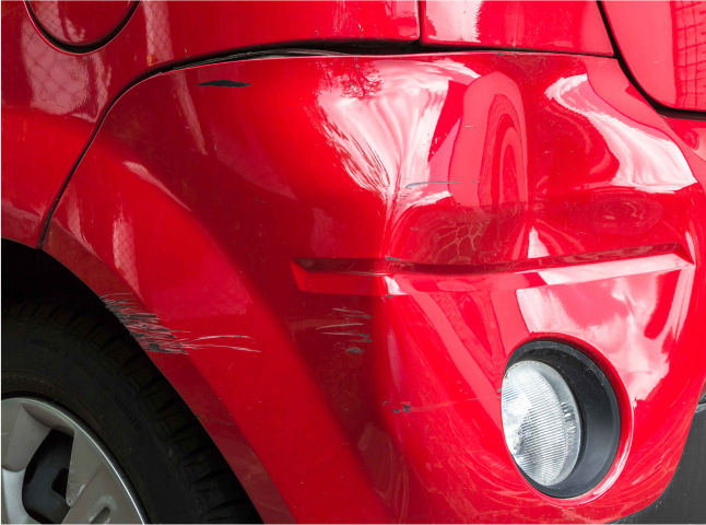 A dented car sits in an auto repair shop, waiting to be fixed
